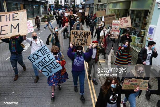 Protesters march through the streets on March 20, 2021 in Truro, England. Protests are taking place across the United Kingdom to call for the Police,...