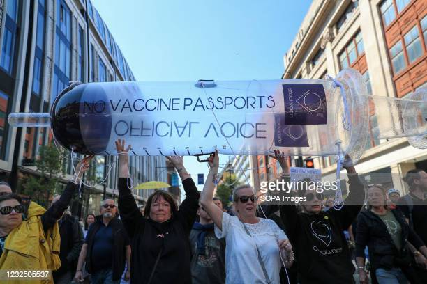 Protesters march through the Streets while holding a blow up syringe during the demonstration. People called online to a flash mob-style mass...