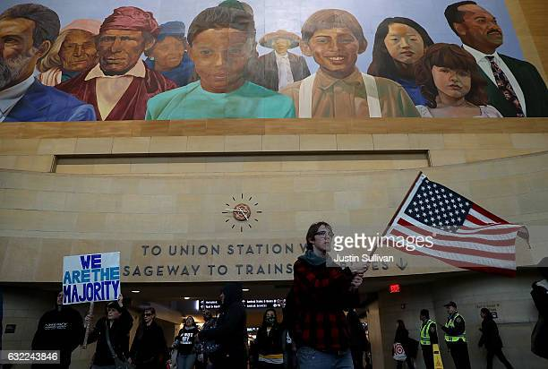 Protesters march through Union Station during a demonstration against US President Donald Trump on January 20 2017 in Los Angeles California Hundreds...