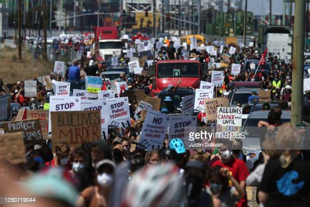 Protesters march towards downtown Oakland during a Juneteenth rally and march at the Port of Oakland on June 19 2020 in Oakland California Thousands...