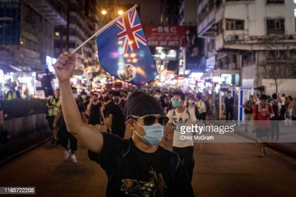 Protesters march towards the Mong Kok district after attending a demonstrati on at West Kowlo on railway stati on protesting against the proposed...