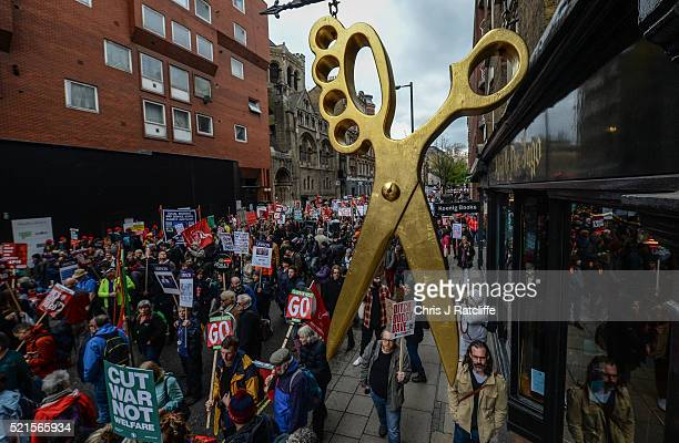 Protesters march under a giant pair of scissors outside a hairdressers during a march for 'Health Homes Jobs and Education' on April 16 2016 in...