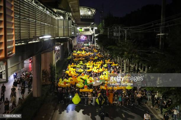 Protesters march while carrying inflatable yellow ducks outside the headquarters of the 11th Infantry Regiment on November 29, 2020 in Bangkok,...