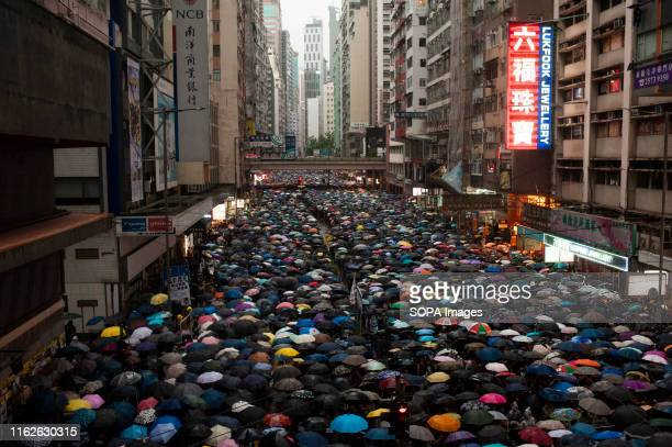 Protesters march while holding umbrellas during the demonstration Over 1 million Hong Kongese protesters filled the streets of Hong Kong Island to...