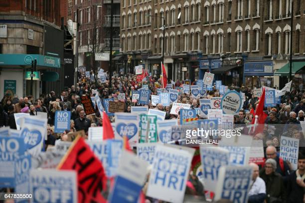 Protesters march with banners and placards against private companies' involvement in the National Health Service and social care services provision...