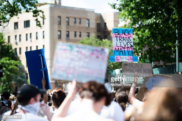 Protesters march with chants, flags, sign and white clothing in support of Black Trans Lives Matter on June 14, 2020 in the Brooklyn borough of New...