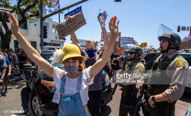 Protesters march with hands up past Los Angeles Sheriff's deputies on Santa Monica Blvd. To demand justice for the killing of George Floyd during...