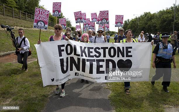 Protesters march with placards to an entrance to the Eurotunnel terminal in Folkestone south east England on August 1 during a gathering in support...