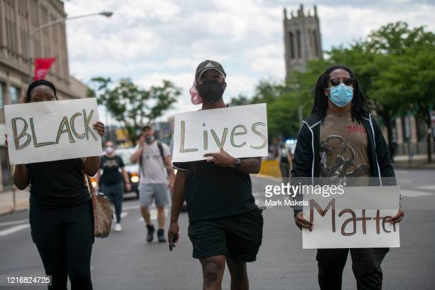 Protesters march with three placards stating BLACK Lives Matter in the aftermath of widespread unrest following the death of George Floyd on June 1...