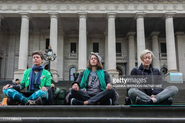 Protesters meditate outside the Victoria state parliament building to mark the beginning of the Extinction Rebellion protests in Melbourne on October...