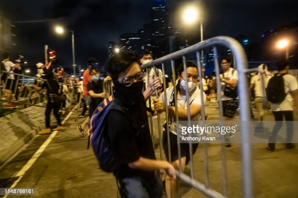Protesters move barricade during a clash at Legislative Council after a rally against the extradition law proposal at the Central Government Complex...
