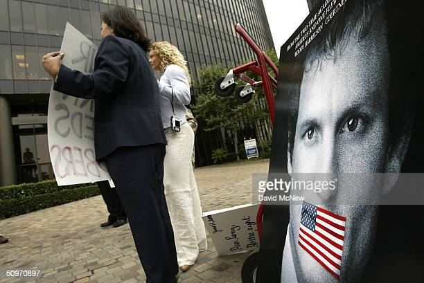 Protesters next to a 'one sheet' for the film 'The People vs Larry Flynt' call on pornography executive Larry Flynt to voluntarily adopt a 100%...