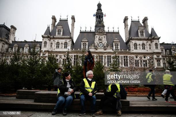 Protesters of the French 'yellow vests' movement sit in front of the Hotel de Ville in central Paris on December 22 2018 during a protest as the...