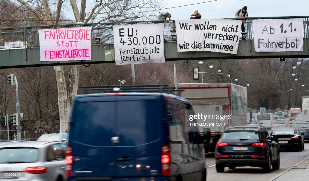 Protesters on a bridge hold banners to protest against particulate pollution as vehicles drive on a busy road on February 1, 2018 at a traffic junction of the Neckartor roadway, a Stuttgart neighbourhood which is a hotspot for air pollution. The banner (C) reads 'driving bans save lives' and 'stop the traffic now'. A court is to rule on February 21, 2018 on whether cities in Germany can ban certain diesel cars to reduce air pollution in their most contaminated areas, a decision that could have far-reaching consequences for transport policy and for the vital industry. /