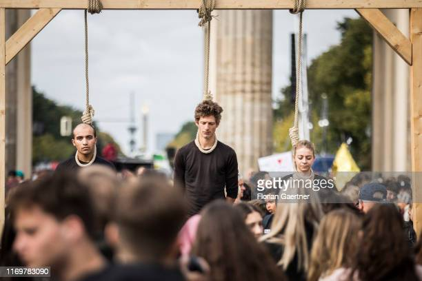 Protesters on a gallow standing on ice are pictured within the worldwide movement 'Fridays for Future' near the Brandenburg Gate on September 20 2019...