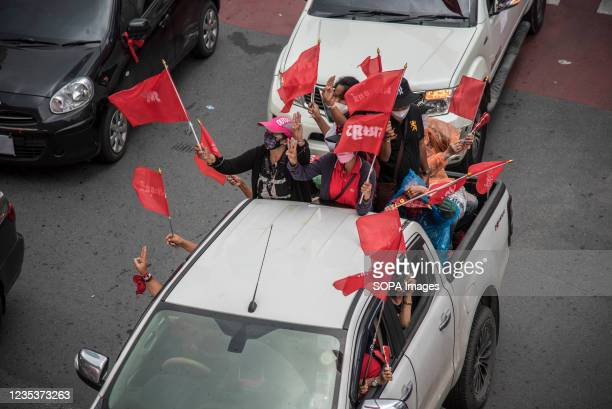 Protesters on a truck seen waving flags during the car mob rally. Anti-government protesters gathered at Asok intersection before they drove their...