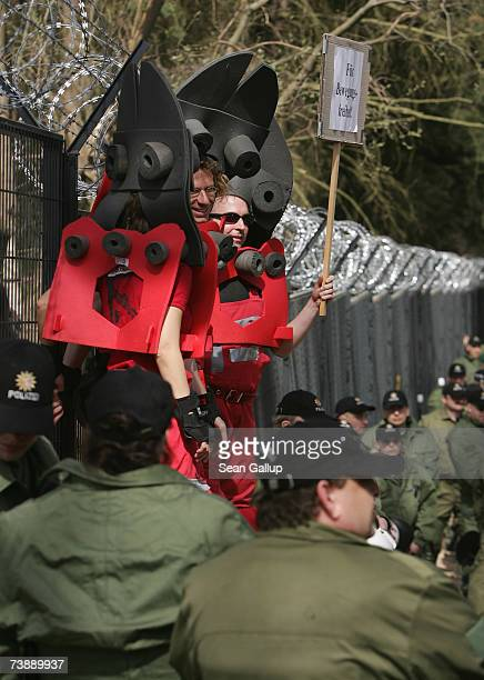 Protesters on stilts dressed as wirecutters stand among riot police standing guard at a section of a 14km long security fence around the German...