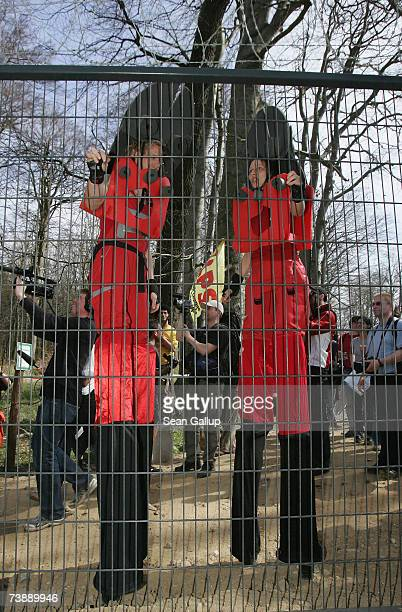 Protesters on stilts dressed as wirecutters stand at a section of a 14km long security fence around the German resort town of Heiligendamm which will...