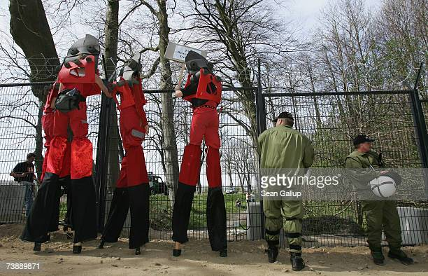 Protesters on stilts dressed as wirecutters walk by riot police standing guard at a section of a 14km long security fence around the German resort...