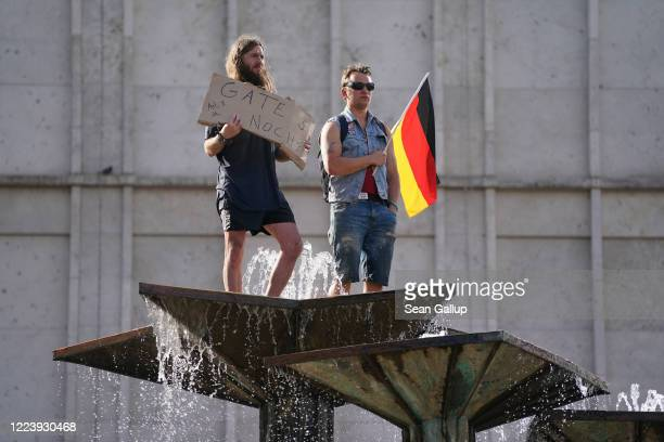 Protesters one holding a sign referring to Bill Gates the other a German flag stand on a water fountain during a protest rally against coronavirus...