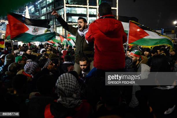 Protesters one shouting slogans wave Palestinian flags on December 12 2017 during a demonstration in front of Berlin's main train station to protest...