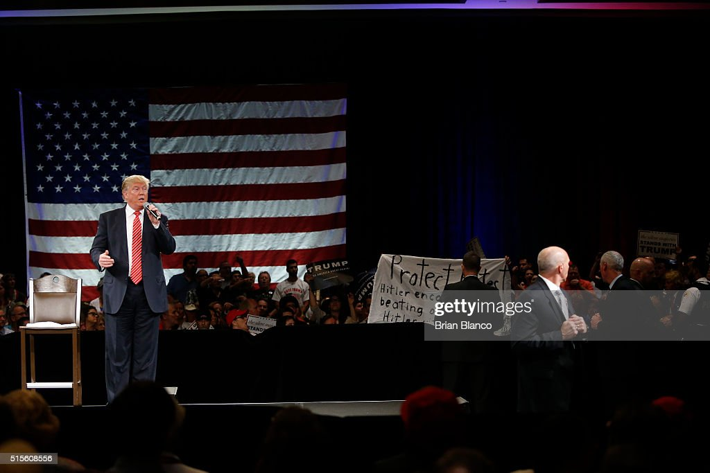Protesters open up a banner as Republican presidential candidate Donald Trump speaks to supporters during a town hall meeting on March 14, 2016 at the Tampa Convention Center in Tampa , Florida. Trump is campaigning ahead of the Florida primary on March 15.