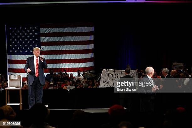 Protesters open up a banner as Republican presidential candidate Donald Trump speaks to supporters during a town hall meeting on March 14 2016 at the...