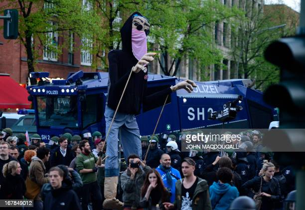 Protesters operate a giant puppet dressed a a demonstrant as they take part in the 'Revolutionary' May Day demonstration on May 1 2013 in Berlin...