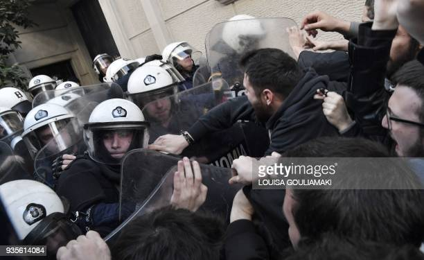 Protesters opposing properties auctions scuffle with riot police outside of a public notary's office in Athens on March 21 2018 Protesters oppose the...
