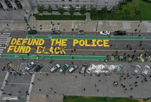 Protesters paint a mural that says 'defund the police' during a Strike For Black Lives demonstration outside of San Francisco City Hall on July 20,...