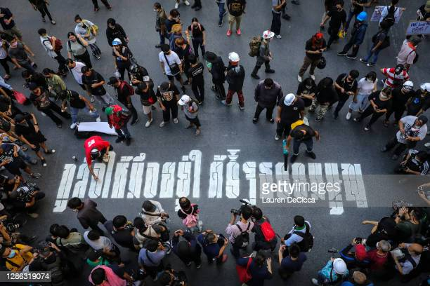 """Protesters paint graffiti that reads """"I ordered you to stay under the constitution"""" at the Ratchaprasong Intersection on November 18, 2020 in..."""