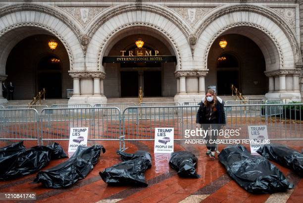Protesters part of a People's Motorcade stop at the Trump International Hotel to deliver fake body bags during a protest against the administration's...