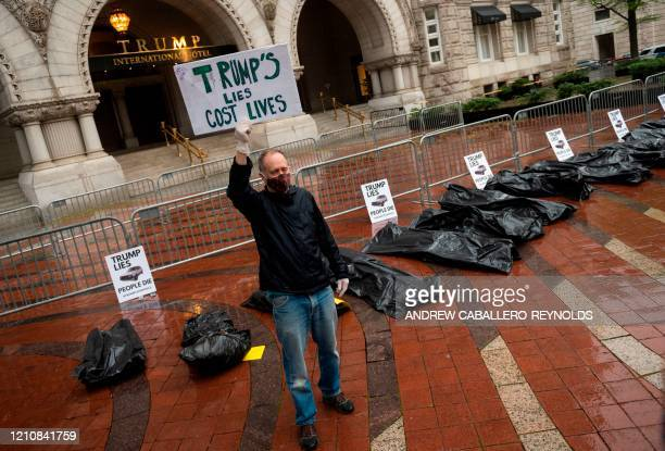 TOPSHOT Protesters part of a People's Motorcade stop at the Trump International Hotel to deliver fake body bags during a protest against the...