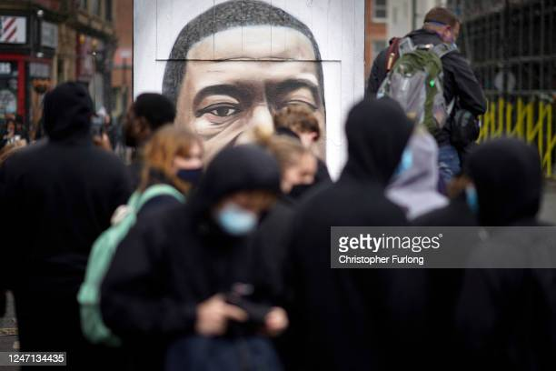 Protesters pay their respects by a street art portrait of George Floyd during a second day of Black Lives Matter demonstrations in Piccadilly Gardens...