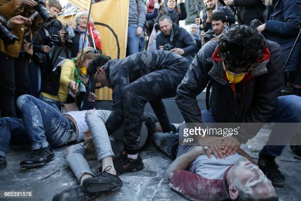 Protesters perform as victims and rescuers as they simulate a chemical attack during a demonstration against chemical attacks in Syria on April 6...
