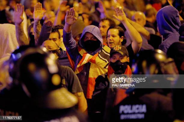 Protesters perform the fascist salute in front of police during a prounion demonstration called by farright collectives in Barcelona on October 17...