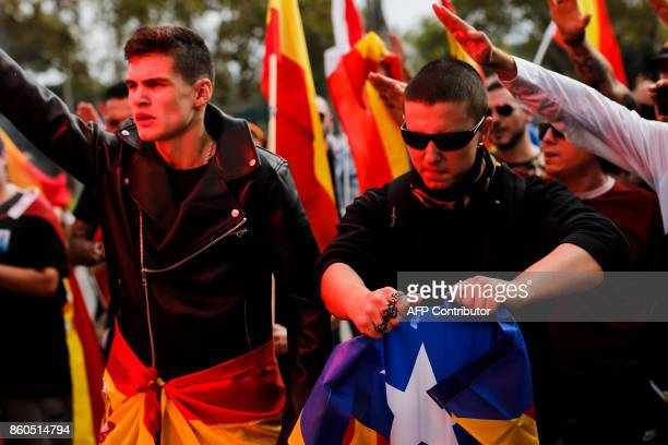 Protesters perform the fascist salute while a man tears an 'Estelada' Catalan proindependence flag during an ultraright wing antiseparatist...