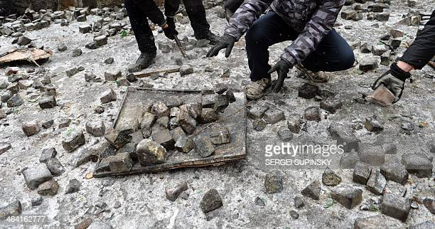 Protesters pick up cobblestones thrown at police in anticipation of future fights with the riot forces in Kiev on January 21 2014 After a night of...