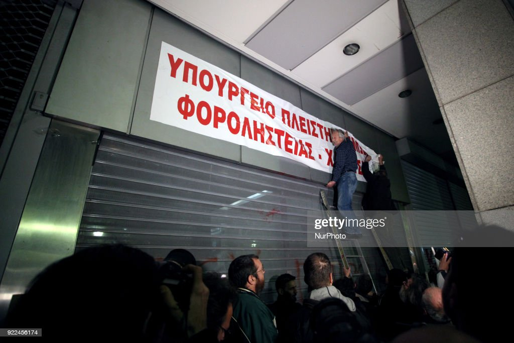 "Protesters place a banner at the entrance of the ministry of economics reading ""ministry of auctions and tax robbery"" during a demonstration against online auctions of foreclosed properties in Athens, Greece on February 21, 2018. A rally against online auctions of foreclosed properties was held in central Athens by labor unions affiliated to the Greek Communist Party (KKE)."
