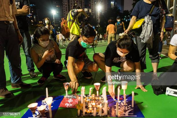 Protesters place candles on posters to avoid leaving wax marks on the playing grounds of Victoria park in Hong Kong, China, on June 4, 2020.