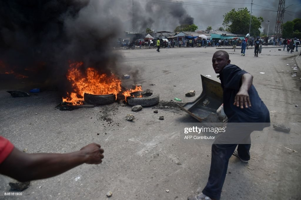 Protesters place debris next to burning tires during anti-government protests in the centre of the Haitian capital Port-au-Prince, on September 12, 2017. Demonstrators took to the streets to protest against the government and the new budget for 2017-2018, throwing stones at the police, setting tires on fire and blocking some streets. /
