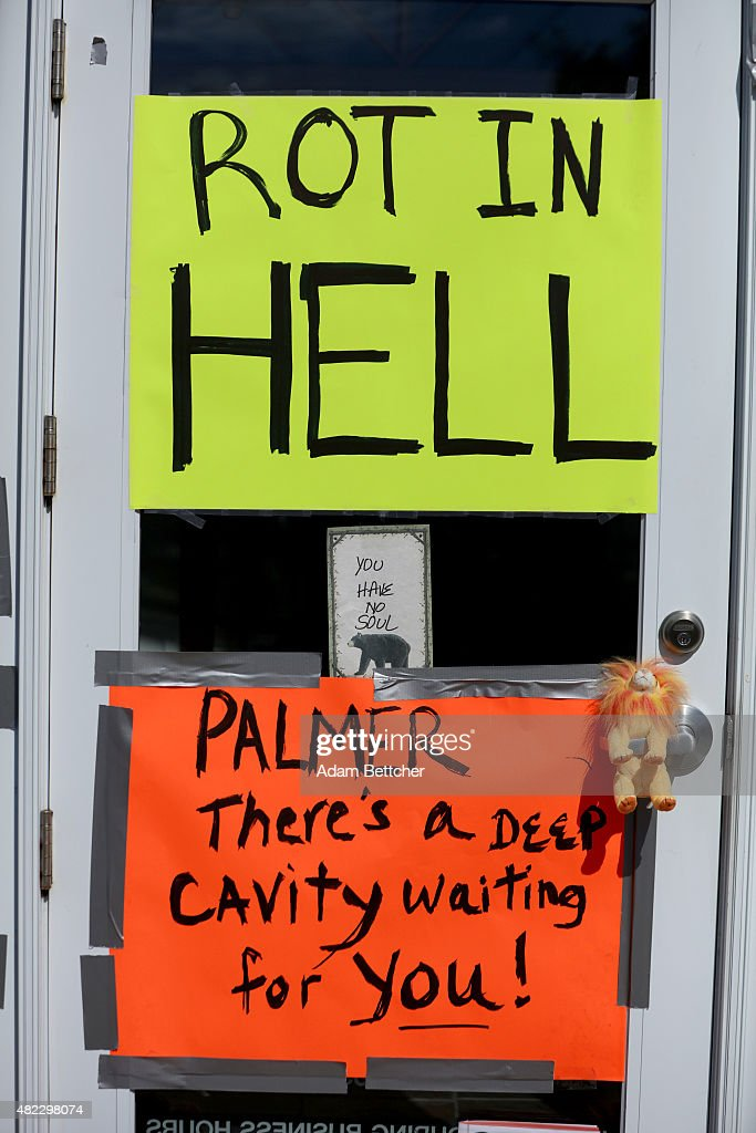 Protesters place signs on the doors of Dr. Walter Palmer's River Bluff Dental Clinic to call attention to the alleged poaching of Cecil the lion on July 29, 2015 in Bloomington, Minnesota. According to reports, the 13-year-old lion was lured out of a national park in Zimbabwe and killed by Dr. Palmer, who had paid at least $50,000 for the hunt.
