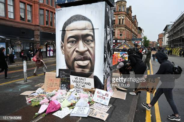 Protesters place their placards at the base of a mural of George Floyd by street artist Akse following a demonstration in Manchester northern England...