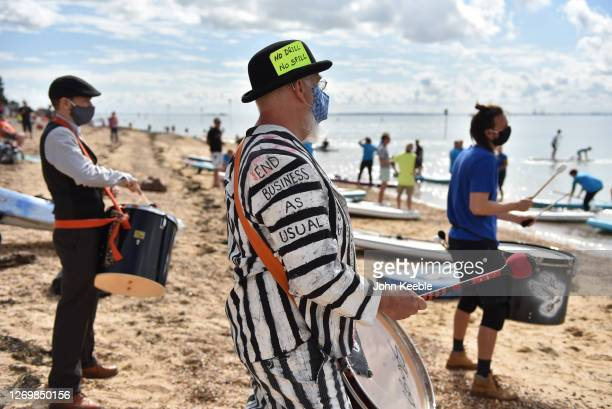 Protesters play drums as Extinction Rebellion protesters stage a Titanicthemed dinner party in the sea to illustrate the threat of rising sea levels...