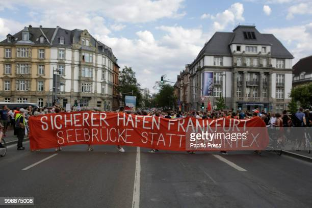 Protesters pose with banners and signs at the large Euro sign outside the former seat of the ECB Around 800 protesters marched through Frankfurt to...