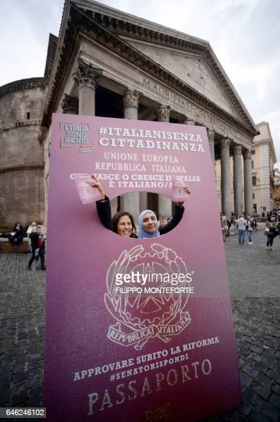 Protesters poses behind a placard representing an Italian passport during a demonstration to ask for a reform of the citizenship law in Italy, on...