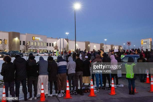 Protesters pray during a rally at the Amazon fulfillment center in Shakopee Minnesota on December 14 2018 A group of Amazon workers in Minnesota who...
