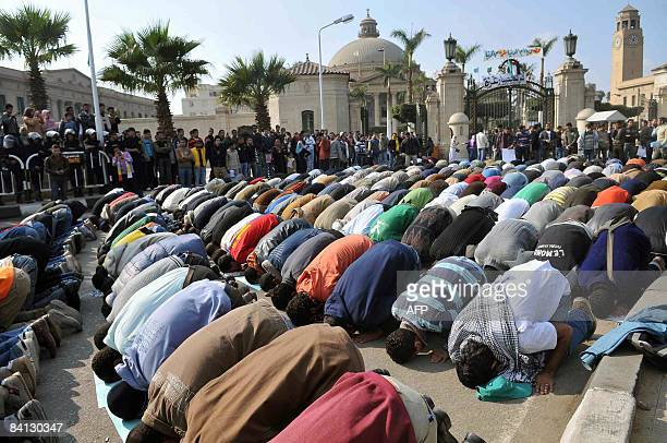 Protesters pray for the dead during a demonstration outside the Cairo University main campus in the Egyptian capital on December 28 2008 against...