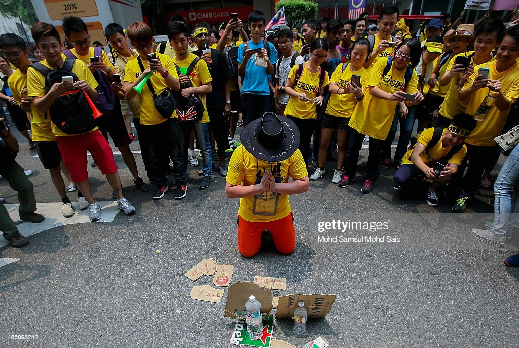 Protesters pray in front a placard message during a Bersih (Clean) rally as protestors call for the resignation of Prime Minister Najib Razak on August 30, 2015 in Kuala Lumpur, Malaysia. Prime Minister Najib Razak has become embroiled in a scandal involving state fund debts and allegations of deposits totaling 2.6 billion ringgit paid to his bank account. Thousand of people gathered to demand his resignation and a new general election.