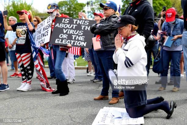 Protesters pray near Governor Charlie Baker's residence during a Reopen Massachusetts Rally on May 16, 2020 in Boston, Massachusetts. The coronavirus...
